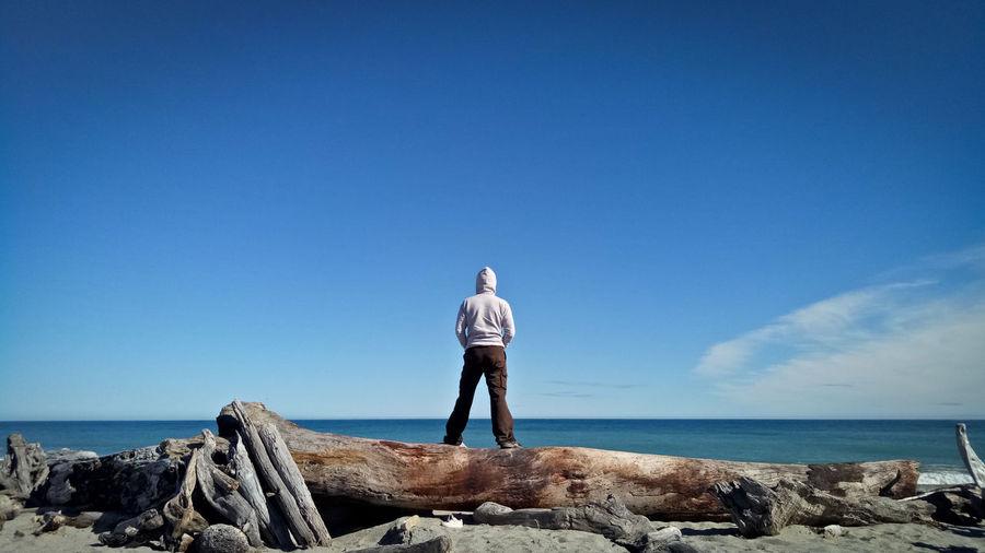 Rear view of man standing on fallen tree trunk by sea against sky