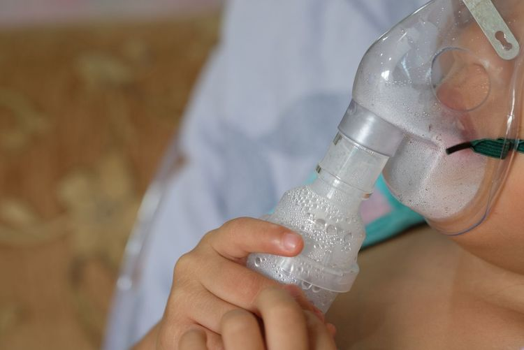 Midsection of patient inhaling through oxygen mask in hospital