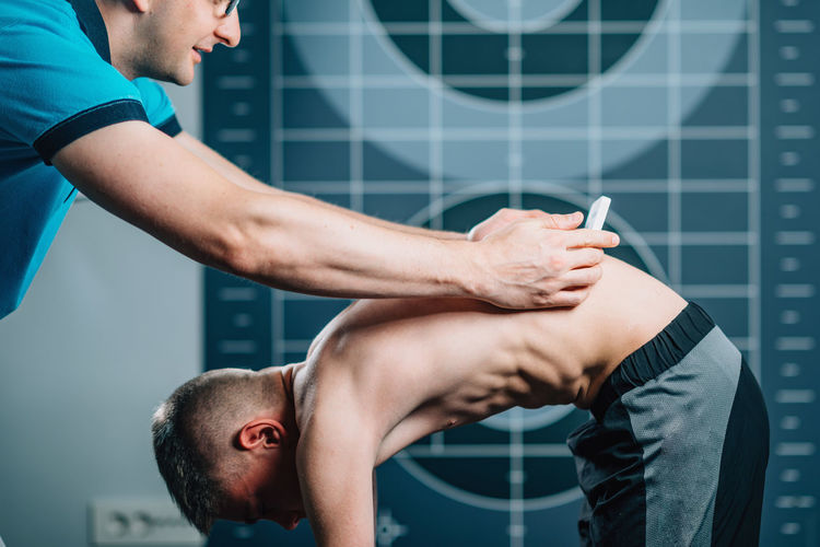 Cropped image of man with male athlete bending in health club