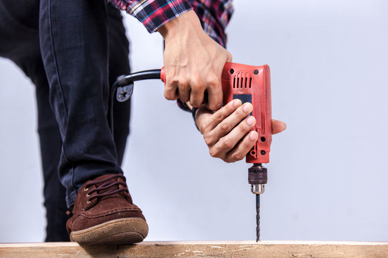 Midsection of man drilling nail on table Adult Close-up Construction Worker Day Focus On Foreground Hand Tool Human Body Part Human Hand Low Section Maintenance Engineer Manual Worker Men Occupation One Person Outdoors People Real People Standing Work Tool