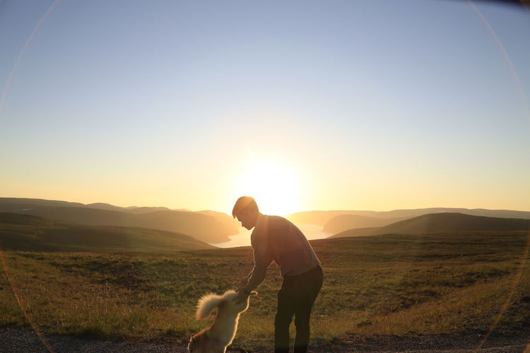Rear view of woman with dog on field against sky during sunset