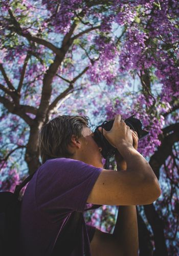 Low angle view of man photographing purple flowering tree