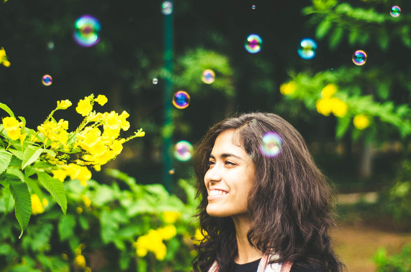 Close-Up Of Smiling Young Woman With Bubbles In Park