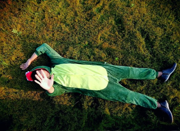 High angle view of man in green mascot lying on land