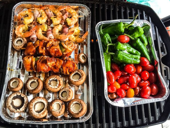 High angle view of food in containers over barbecue grill