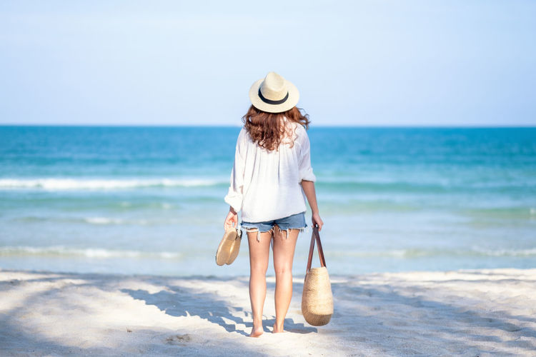 A woman holding bag and shoes while strolling on the beach with the sea and blue sky background Sun Summer Strolling Stroll Standing Space Sky Shoes Sea Sand Relaxation Relax People Outdoor Ocean Nature Look Lifestyle Leisure Lady Holiday Holding Hat Happy Girl Fresh Female Coast Clouds Blue Beauty Beautiful Beach Bag Background Back Attractive Asian  Adult