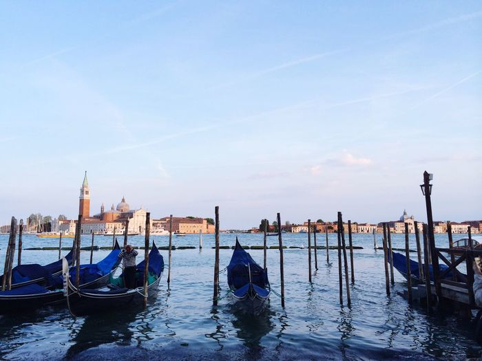 Gondolas moored on grand canal against blue sky