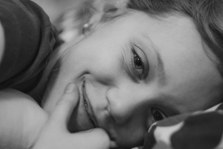 Close-up portrait of girl smiling while lying on bed