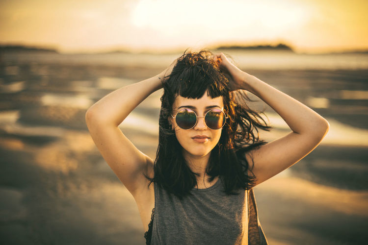 Portrait of smiling young woman standing at beach during sunset