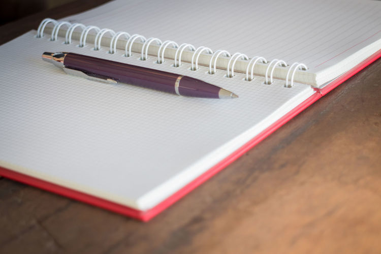 High angle view of pen and diary on table