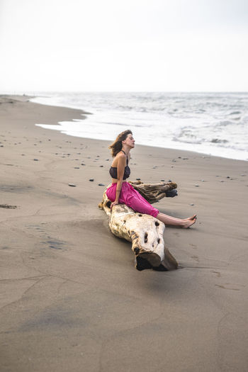 Side View Of Young Woman Sitting On Driftwood On Shore At Beach