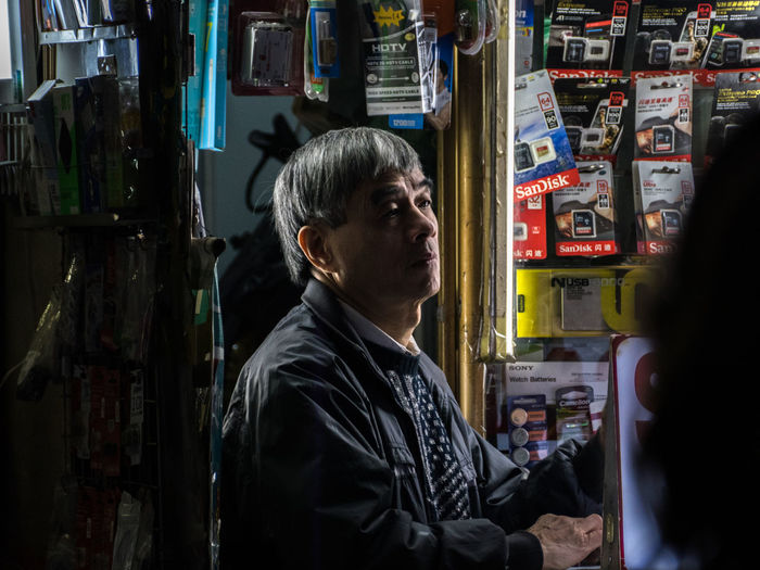 Moment of absence. Dreamy man illuminated by his shop in Hanoi Men Real People Portrait One Person City Headshot Waist Up Side View Mature Adult Architecture Standing Looking Store Profile View Absence Dreaming Dreamy Candid Photography Candid Portraits Shop Light And Shadow Available Light Documentary ASIA