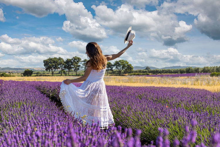 Woman seen from behind plays with her long white dress in the middle of a blooming lavender field.