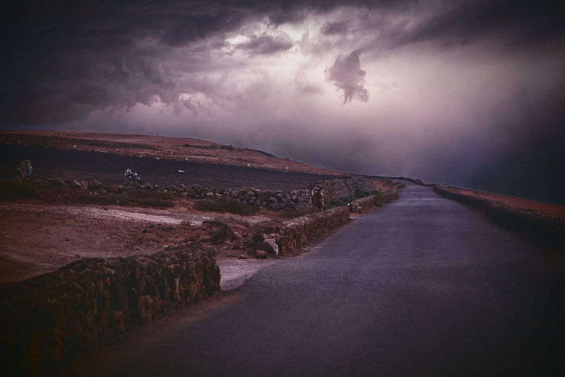 Road amidst land against sky at dusk
