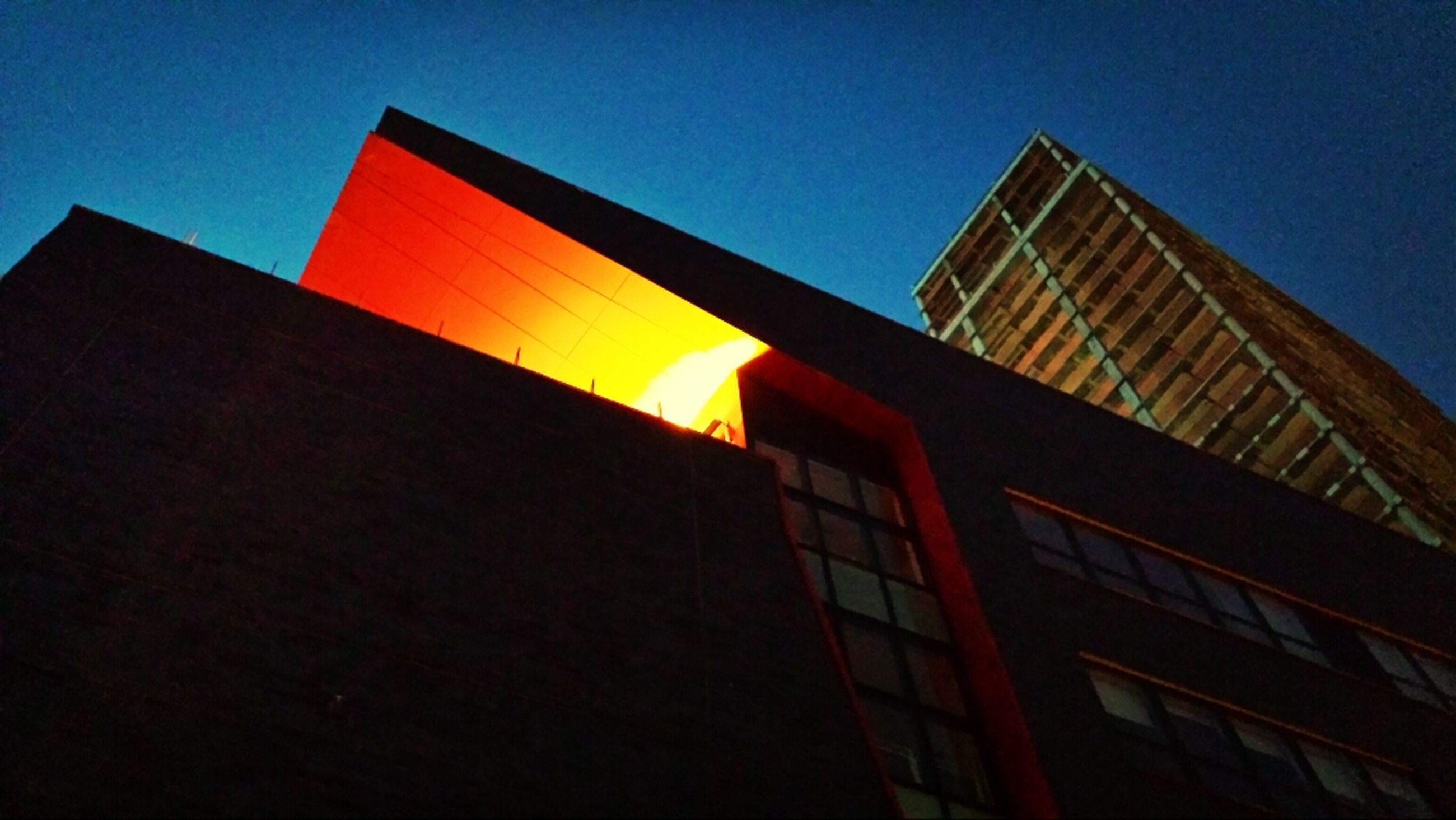 building exterior, architecture, built structure, low angle view, clear sky, blue, building, window, city, sky, residential structure, residential building, sunlight, outdoors, no people, sunset, orange color, tower, day, tall - high