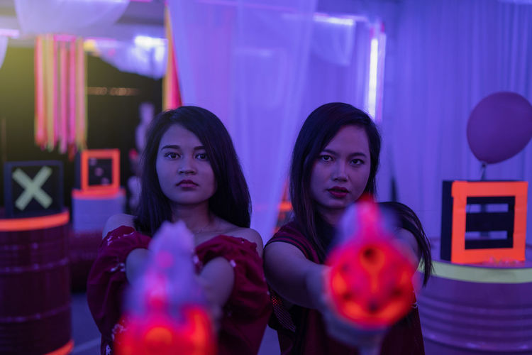 asian teenage playing laser gun Young Adult Portrait Indoors  Women Adult Young Women Two People Front View Nightlife Lifestyles People Looking At Camera Leisure Activity Friendship Long Hair Headshot Enjoyment Togetherness Hairstyle Beautiful Woman