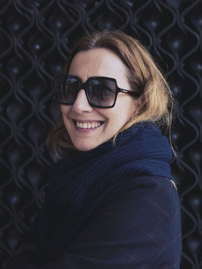 Portrait of a smiling young woman wearing sunglasses