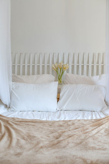 Pillows on bed against wall at home