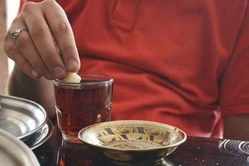 Close-Up Of Man Dipping Cookie In Tea On Table