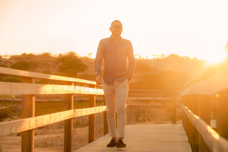 Man standing on railing against sky during sunset