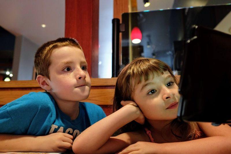 Close-up of siblings using digital tablet at table