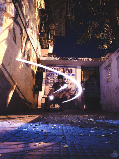 Man sitting on footpath by street against buildings at night