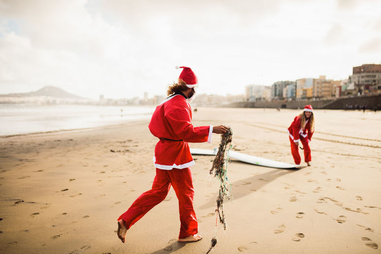 Couple wearing santa costumes at beach against sky