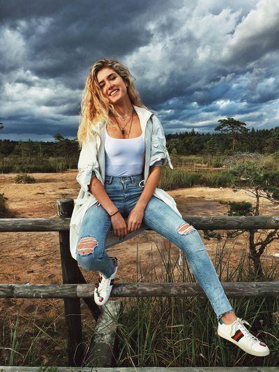 Full length portrait of happy woman sitting on field