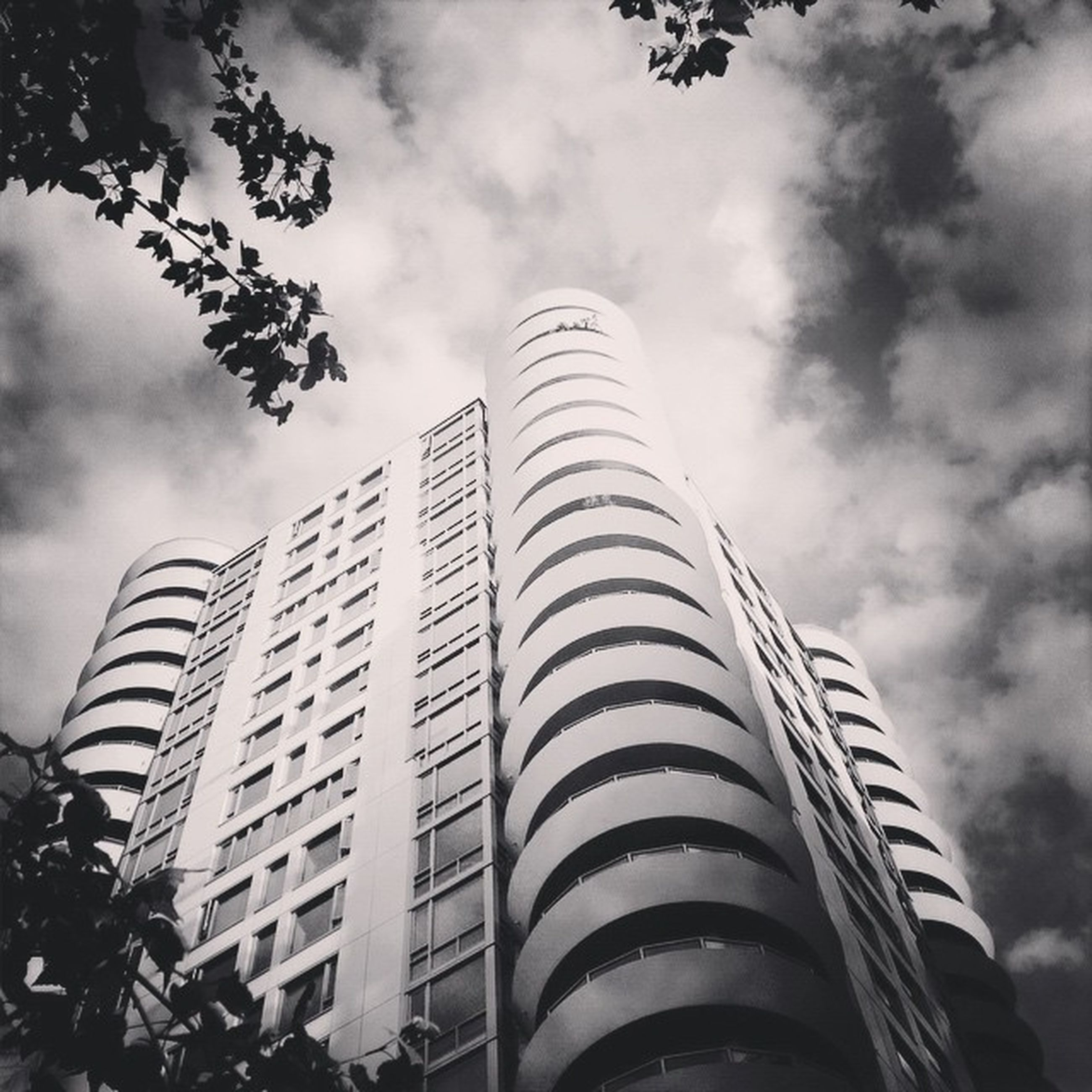 building exterior, architecture, built structure, low angle view, sky, cloud - sky, modern, city, tall - high, skyscraper, cloudy, office building, tower, building, cloud, tree, tall, outdoors, day, growth