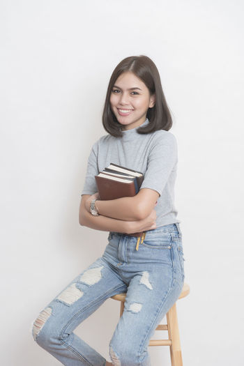 A portrait of an Asian university student on white background Adorable ASIA Beautiful Book Colleagues Cute Education School Smile Studio Studio Photography Teen Teenager University Woman Young Adult Young Women