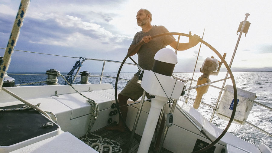 Man Steering Yacht In Sea