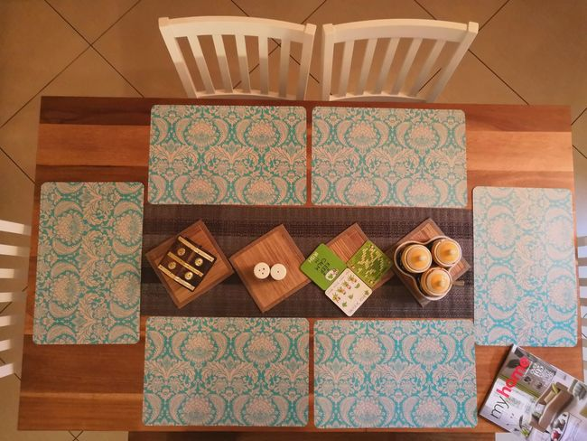 Wooden Dining Table with blue mats EyeEmSelect Dining Table Wooden Table Mat Table Coaster Floral Pattern Floral White Chair Organised Organized Organized Chaos Neat Neatly Arranged Salt Pepper Magazine Myhome Tile Palette Home Showcase Interior Model Home Tidy Room Holiday Villa Penthouse Tiled Floor