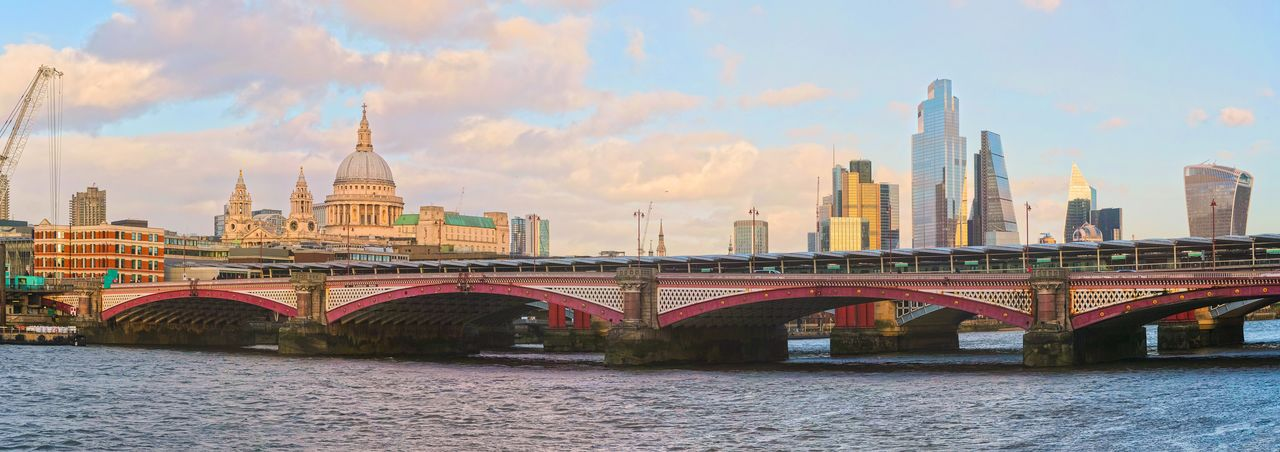 Bridge over river against buildings in city