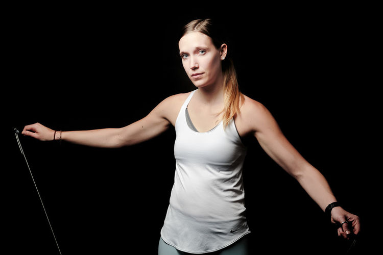 Young woman looking away while standing against black background Adult Sport Activity Athletic Attractive Beautiful Body Exercise Female Fit Fitness Girl Gym Health Healthy Lifestyle Muscle One person Pilates Pose Slim Sportswear Studio Training Weight Wellness Woman Workout Young Black Background Studio Shot One Person Front View Young Adult Young Women Indoors  Standing Three Quarter Length Sports Clothing Looking At Camera Hair Lifestyles Women Healthy Lifestyle Tank Top Looking Beautiful Woman Hairstyle