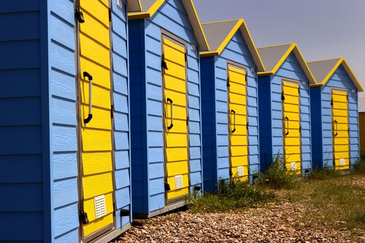 Beach huts along the coastline of a tourist beach in England England, UK Holiday In A Row Travel Travel Photography Architecture Beach Hut Blue Building Building Exterior Built Structure Clear Sky Day Entrance Huts In A Row Multi Colored Multi Colored Sky No People Outdoors Side By Side Timber Huts Vacation Wood - Material Yellow