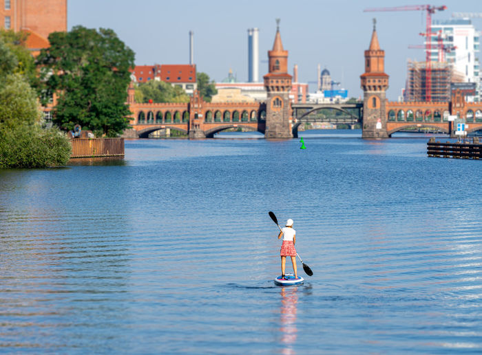 Rear view of man in river against sky in city