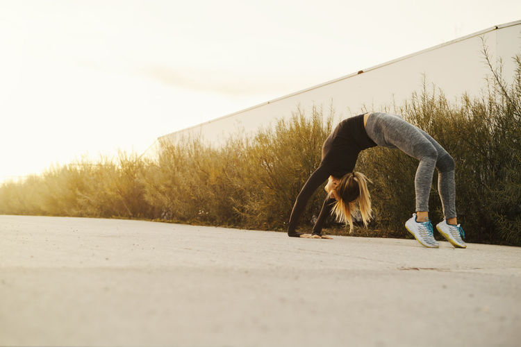 Young fit athletic woman warming up at sunset in urban environment Balance Day Exercising Flexibility Full Length Handstand  Healthy Lifestyle Leisure Activity Lifestyles Nature One Person Outdoors Real People Relaxation Exercise Side View Sky Sport Stretching Women Workout Yoga Young Adult