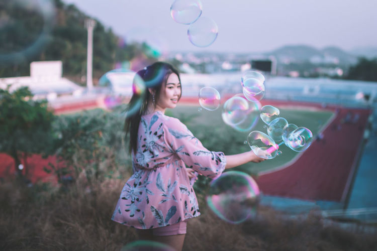 never lose your sense of wonder. Beautiful Woman Blowing Bubble Bubble Wand Casual Clothing Cheerful Day Enjoyment Flying Focus On Foreground Fragility Fun Happiness Holding Leisure Activity Lifestyles Mid-air Motion Nature One Person Outdoors Real People Smiling Young Adult Young Women