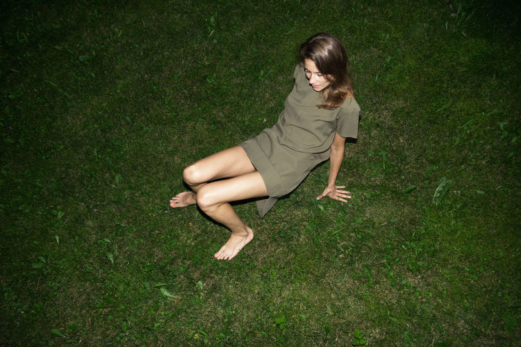 High Angle View Of Young Woman Sitting On Grassy Field At Night