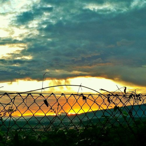 Chainlink fence on field against cloudy sky