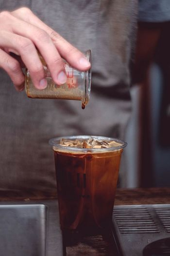 Midsection of person pouring iced coffee in glass