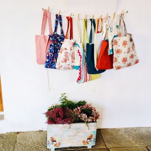 Bags hanging over potted plant against wall