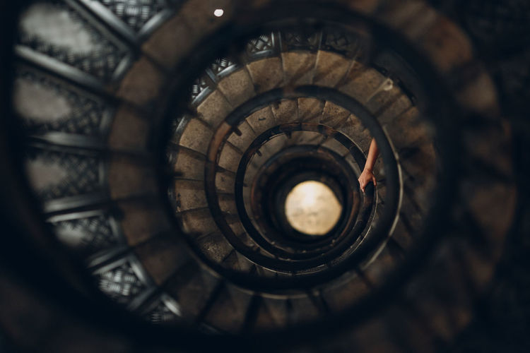 Directly above shot of spiral staircase with hand on railing