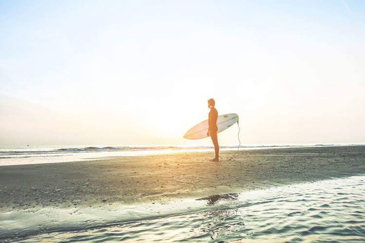 Full Length Of Man With Surfboard Standing On Beach Against Sky