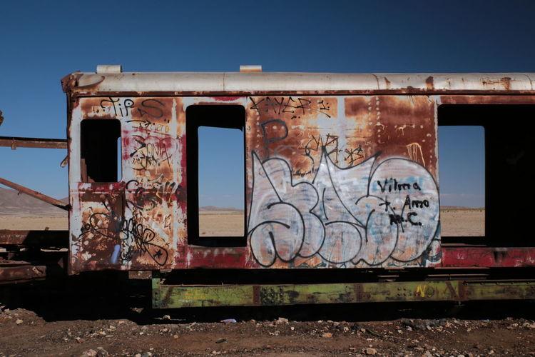 Graffiti on abandoned train against sky