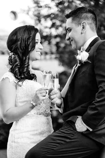 Smiling bride and groom toasting champagne flutes while standing outdoors