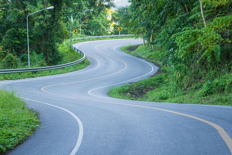 Road curves up the mountain in Thailand Road Plant Curve Tree Transportation The Way Forward Direction Sign No People Day Nature Road Marking Green Color Marking Symbol Empty Growth Land Forest Asphalt Winding Road Outdoors Diminishing Perspective Dividing Line Crash Barrier