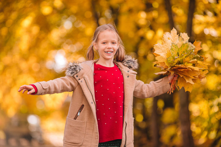 Portrait of a smiling young woman with autumn leaves