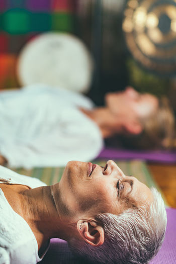 Close-up of mature woman lying with daughter at spa