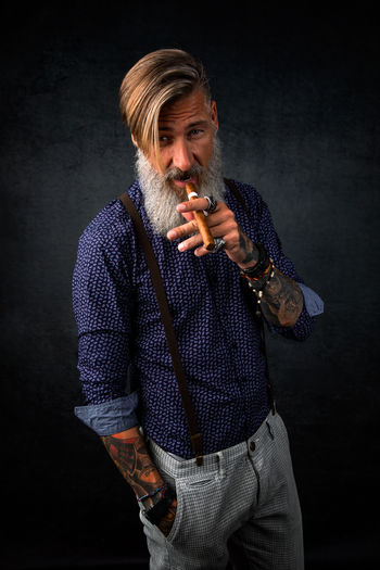 Portrait Of Bearded Man Holding Cigar While Standing Against Black Background